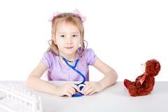 Una niña está jugando - ella está en el papel de un doctor foto de archivo libre de regalías