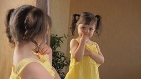 Una niña está mirando en el espejo Una muchacha hermosa con las colas en su cabeza está estudiando la cara del búho Un niño en un almacen de video