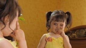 Una niña está mirando en el espejo Una muchacha hermosa con las colas en su cabeza está estudiando la cara del búho Un niño en un almacen de metraje de vídeo