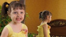 Una niña está mirando en el espejo Una muchacha hermosa con las colas en su cabeza se inclina delante del espejo Un niño en un am almacen de video