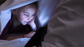 Una niña está mirando un vídeo cubierto con una manta almacen de video