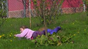 Una niña está rodando en la hierba, carro A cámara lenta almacen de video