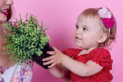 Una niña está sosteniendo un pote con una planta en sus manos fotos de archivo