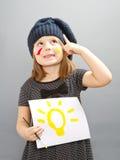 Una niña feliz con un bulbo pintado; concepto de buena idea Imagenes de archivo