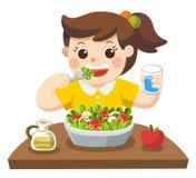 Una niña feliz de comer la ensalada ella ama verduras Fotos de archivo libres de regalías