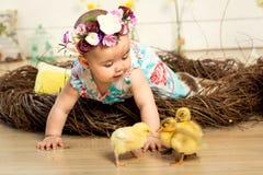 Una niña feliz en un vestido con las flores en su cabeza se está sentando en una jerarquía y anadones mullidos lindos de Pascua y fotografía de archivo libre de regalías