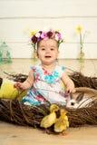 Una niña feliz en un vestido con las flores en su cabeza se está sentando en una jerarquía y anadones mullidos lindos de Pascua y foto de archivo