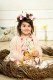 Una niña feliz en un vestido con las flores en su cabeza se está sentando en una jerarquía y está sosteniendo los anadones mullid foto de archivo