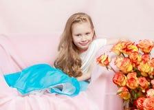 Una niña hermosa con de largo, luz, pelo rizado, en un azul Fotografía de archivo
