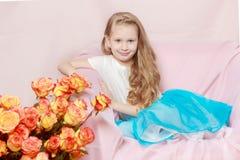 Una niña hermosa con de largo, luz, pelo rizado, en un azul Fotos de archivo libres de regalías