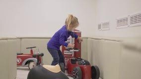 Una niña juega con los coches elegantes hermosos almacen de metraje de vídeo