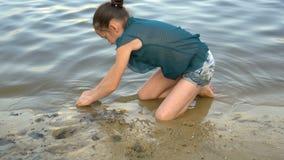 Una niña juega en la playa en la puesta del sol y construye una torre de la arena en el fondo del agua tranquila Retrato cierre almacen de video