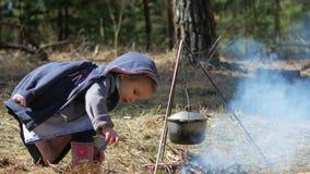 Una niña lanza la madera en la hoguera Independencia y diligencia metrajes