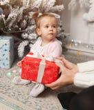 Una niña linda hermosa abre un regalo del Año Nuevo Con el árbol de navidad en el fondo imagen de archivo