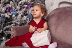 Una niña linda hermosa vestida en un vestido rojo de la tarde elegante se sienta en el sofá y abre un regalo del ` s del Año Nuev foto de archivo