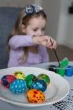Una niña linda que colorea los huevos de Pascua Fotos de archivo libres de regalías