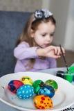 Una niña linda que colorea los huevos de Pascua Foto de archivo