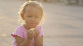 Una niña linda que come una manzana fresca en el parque y que muestra el finger grande para arriba metrajes