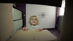 Una niña mira en la caja para recibir una sorpresa El niño abrió una caja metrajes