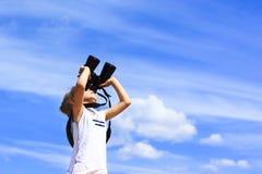 Una niña mira a través de los prismáticos Fondo del cielo azul Esperar un viaje a un país distante Imagenes de archivo