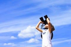 Una niña mira a través de los prismáticos Fondo del cielo azul Esperar un viaje a un país distante Fotos de archivo