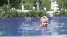 Una niña nada en la piscina afuera almacen de metraje de vídeo