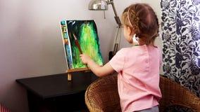 Una niña pinta su imagen con las pinturas y los cepillos almacen de metraje de vídeo