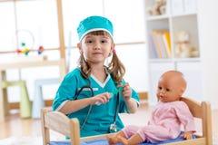 Una niña preescolar activa del niño vestida como juegos del doctor con su muñeca fotos de archivo libres de regalías