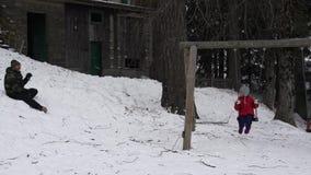 Una niña que balancea en el oscilación mientras que su padre lanza bolas de nieve en ella, 4K almacen de video