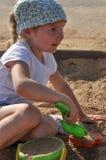 Una niña que juega con la arena en una salvadera Imagenes de archivo