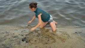 Una niña que juega con la arena mojada en la orilla del río en la puesta del sol que se sienta en sus rodillas Ella recoge las ma metrajes