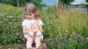 Una niña que juega con un conejo del juguete en el prado entre el trébol floreciente almacen de metraje de vídeo