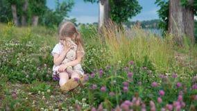 Una niña que juega con un conejo del juguete en el prado entre el trébol floreciente almacen de video
