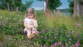 Una niña que juega con un conejo del juguete en el prado entre el trébol floreciente metrajes