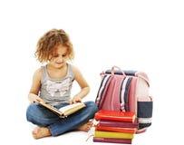 Una niña que lee un libro en el suelo Fotos de archivo libres de regalías