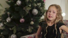 Una niña que llora cerca del árbol El niño está esperando los regalos almacen de metraje de vídeo