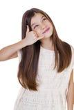 Una niña que me hace una llamada gesto, contra el backgrou blanco Imagen de archivo libre de regalías
