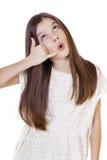 Una niña que me hace una llamada gesto, contra el backgrou blanco Foto de archivo