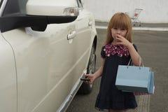 Una niña que se coloca cerca de un coche Fotos de archivo libres de regalías