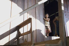 Una niña que se coloca detrás de la puerta en un pueblo de Tailandia Foto de archivo libre de regalías