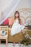 Una niña que se sentaba con los ojos se cerró en la cama fotografía de archivo libre de regalías