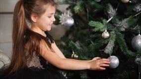 Una niña que se sienta cerca del árbol de navidad juega con una bola del ` s del Año Nuevo que pese en una rama almacen de metraje de vídeo