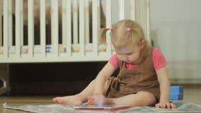 Una niña que se sienta en el piso utiliza una tableta, tocando su finger en la pantalla táctil almacen de metraje de vídeo