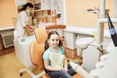 Una niña que se sienta en una silla en la oficina del dentista imagenes de archivo