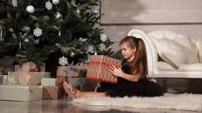 Una niña que sostiene una caja con un regalo de Navidad que ella se sienta en el piso cerca del árbol de navidad almacen de metraje de vídeo