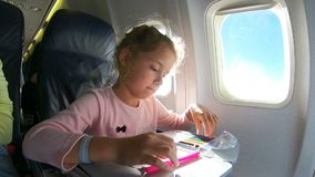 Una niña que viaja por un aeroplano y que dibuja una imagen con los lápices coloridos metrajes
