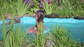 Una niña salta en una pequeña charca, salpicando el agua del salto El niño goza del agua fresca en un día de verano caliente almacen de metraje de vídeo