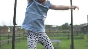 Una niña salta en un trampolín en una cabaña del verano almacen de video