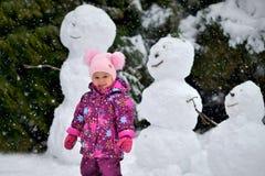 Una niña se coloca cerca de tres muñecos de nieve en el invierno fotos de archivo libres de regalías