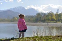 Una niña se coloca cerca del lago en el fondo de montañas imagen de archivo